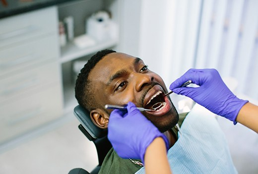 A man lying back in a dentist's chair and allowing his dentist to examine his smile