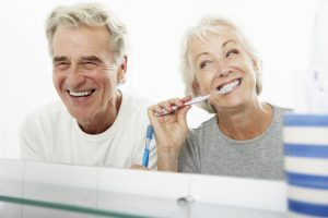 senior couple laughing and brushing teeth