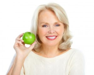 woman smiling preparing eat apple