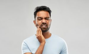 Pained man hand on cheek should see Lynchburg emergency dentist