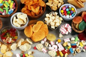 Spread of unhealthy snacks you shouldn't eat after dental implants in Lynchburg
