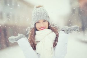 woman smiling in the snow during winter
