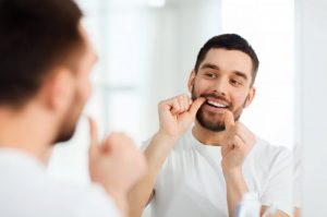 man flossing to prevent a dental emergency